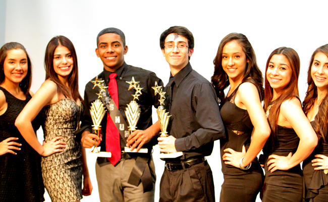 Senior Elijah Perez (middle holding two trophies) poses with other participants and student escorts.  Perez was crowned this year's Hanks Hunk (photo by Ruby Cerino).