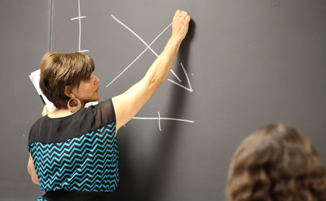 Government teacher Margarita Rodriguez draws something on the board to illustrate a point (photo by Will Jacobo).