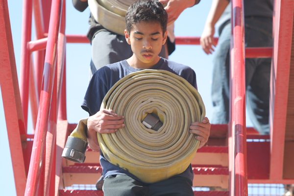 Junior Isaiah Franco carries a fire hose down a ladder at El Paso's Firefighter Academy (photo by Naomi Magallanes).